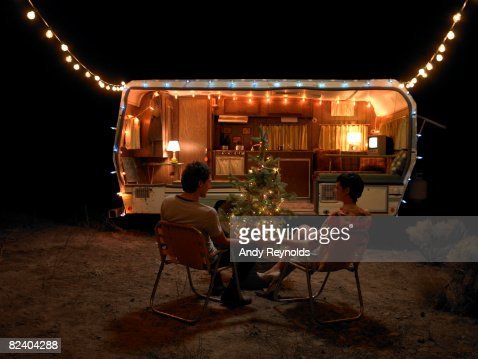 man and woman sitting by tree next to home : Stock Photo