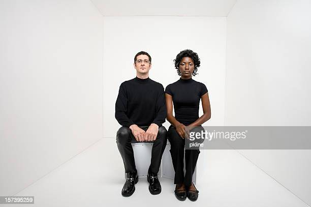 Man and woman sitting in a white room facing camera