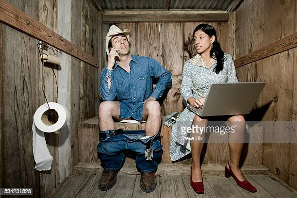 Man and Woman Sitting in an Outhouse
