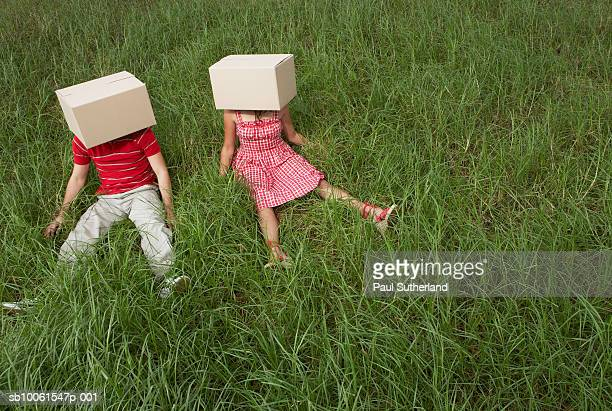Man and woman sitting in grass field with cardboard boxes on heads