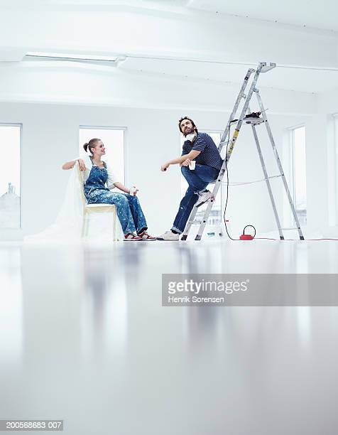 Man and woman sitting in room, taking break from work in apartment