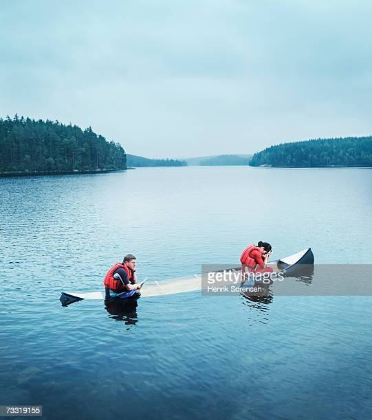 Man and woman sitting in sinking canoe, side view