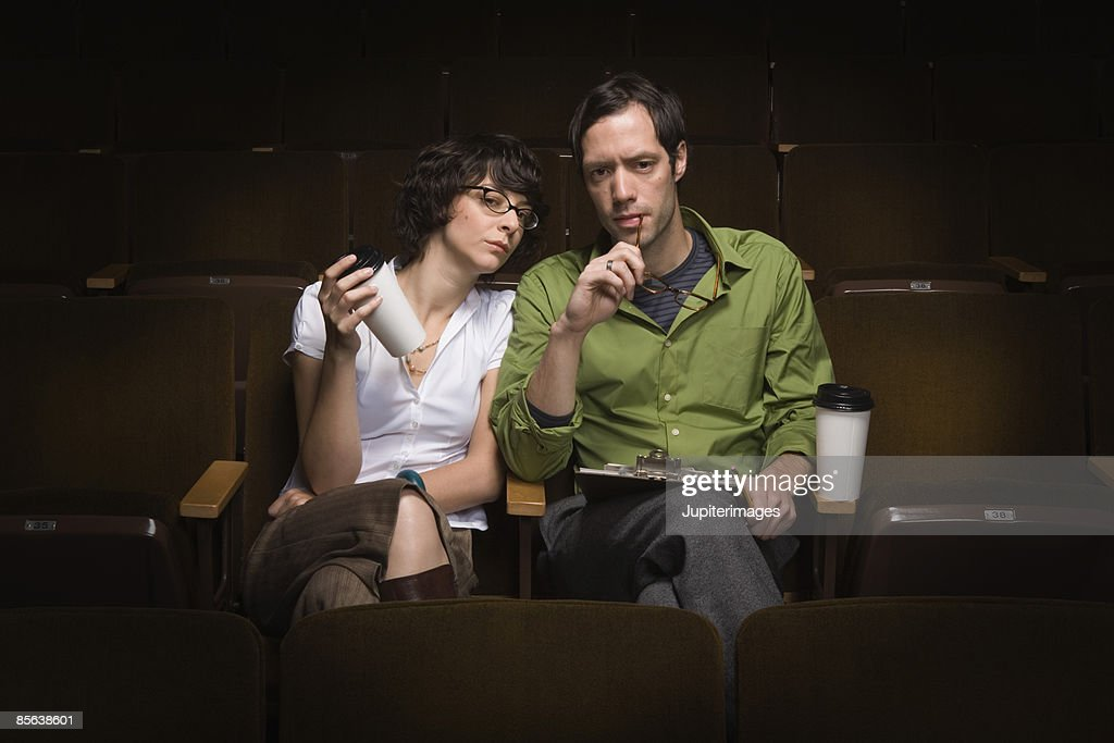 Man and woman sitting in theater conducting casting call,25-30 years,30-35 years,adult,audition,auditorium,beverage,bohemian,brunette,casting,casting call,casting director,casual attire,caucasian,cinema,clipboard,coffee
