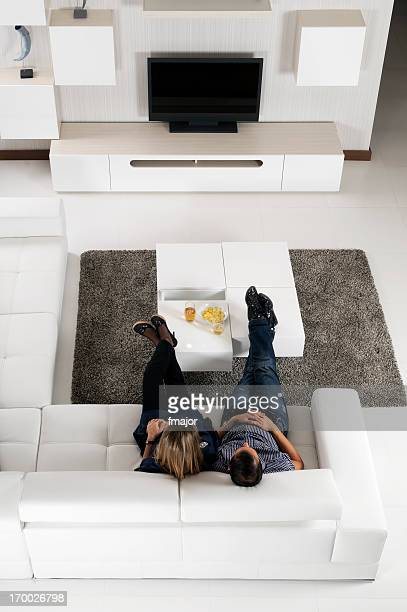 Man and woman sitting in white leather chairs with feet up
