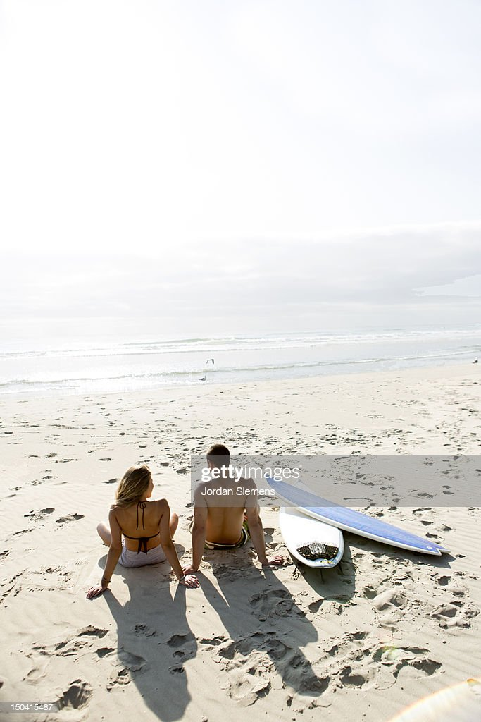 A man and woman sitting next to surfboards. : Stock Photo