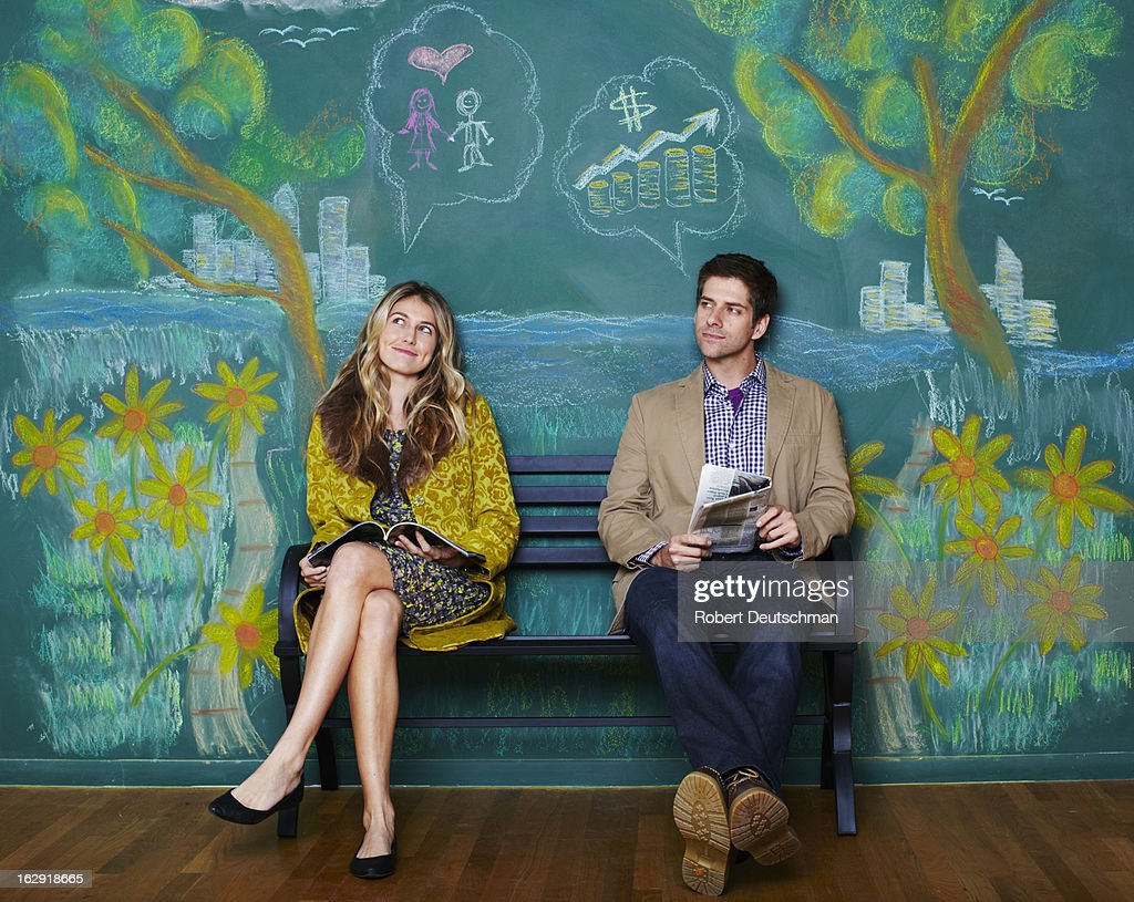 A man and woman sitting on a park bench. : Stock Photo