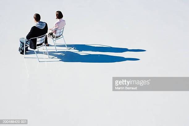 Man and woman sitting on aluminium chairs on platform, rear view