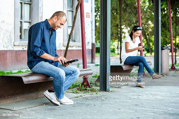 Man and Woman Sitting On Bench Using Phone and Tablet PC, Osijek, Croatia