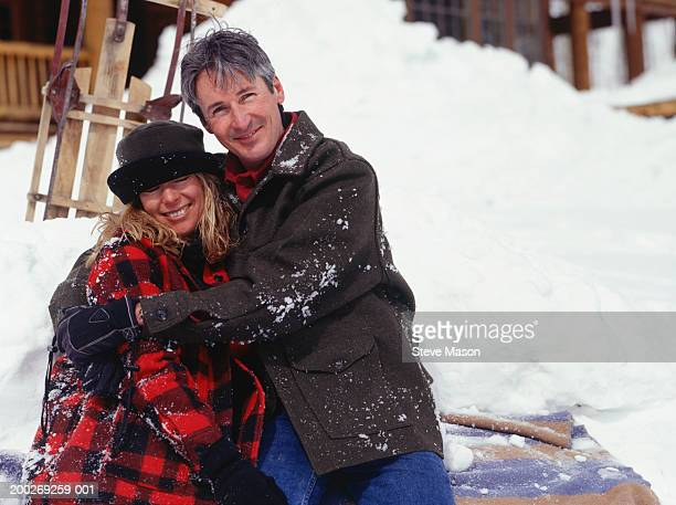 Man and woman sitting on blanket in snow, portrait