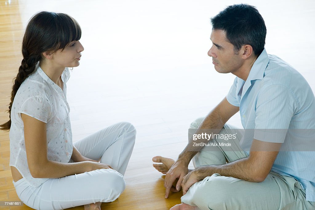 Man and woman sitting on floor, face to face : Stock Photo