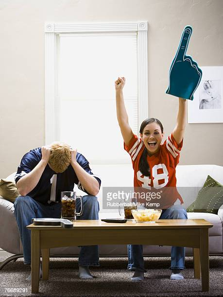 Man and woman sitting on sofa watching football smiling and cheering