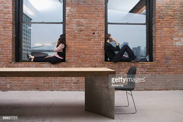 A man and woman sitting on window sills and talking on mobile phones