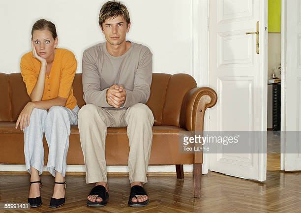 Man and woman sitting side by side on sofa