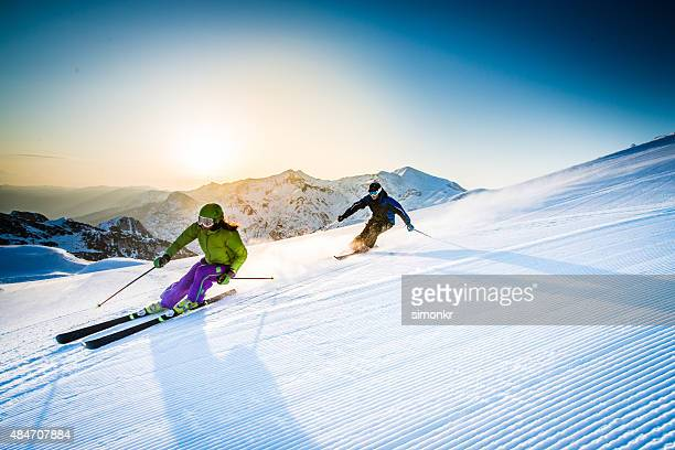 Man and woman skiing downhill