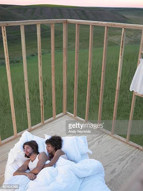 Uomo e Donna che dorme nel letto nella casa frame