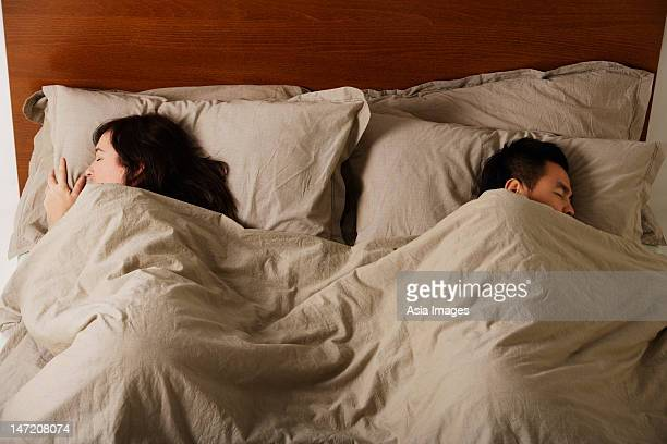 Man and woman sleeping in bed together