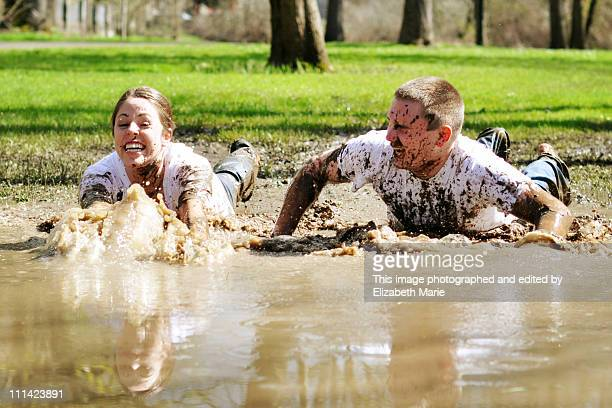 Man and woman sliding into a large mud puddle