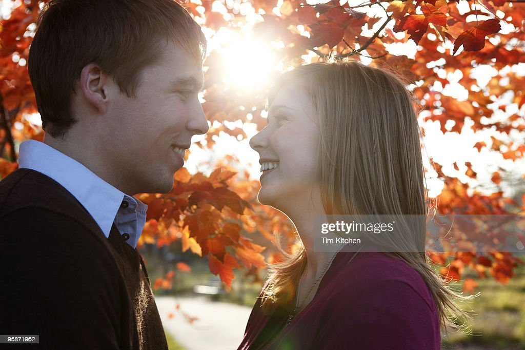 Man and woman smiling under tree, autumn : Stock Photo