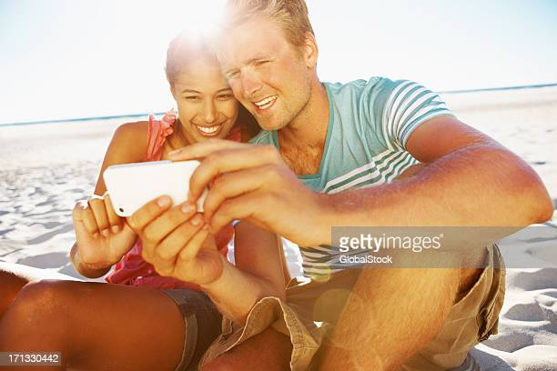 Man and woman smiling while looking at a phone