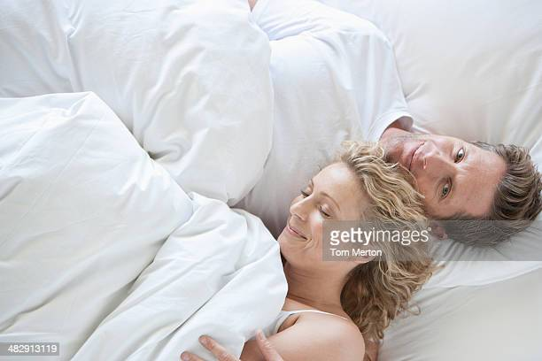 Man and woman snuggling in bed asleep