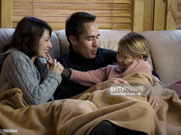 Man and woman snuggling with young girl on sofa with blanket