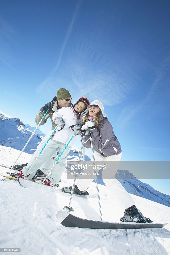Man and Woman Stand on a Ski Slope With Their Young Daughter : Stock Photo