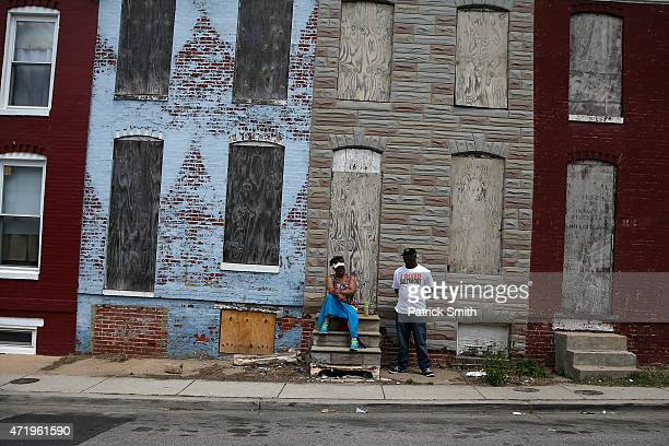 A man and woman stand on the street a day after Baltimore authorities released a report on the death of Freddie Gray on May 2 2015 in Baltimore...