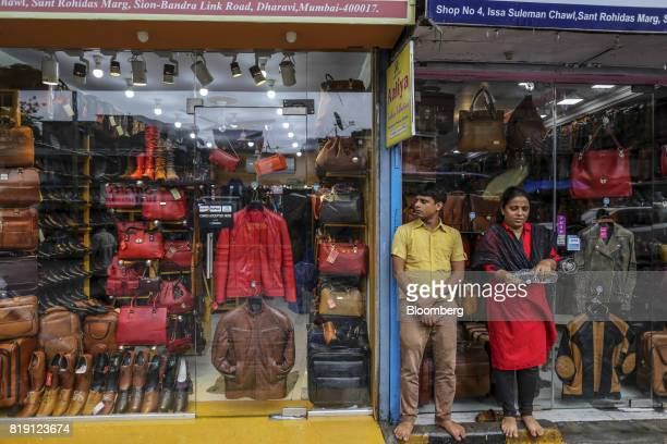 A man and woman stand outside a leather goods store in the Dharavi area of Mumbai India on Tuesday July 18 2017 India's new goods and services tax...