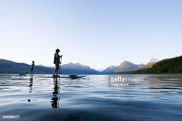 A man and woman stand up paddle boards (SUP) on Lake McDonald in Glacier National Park.