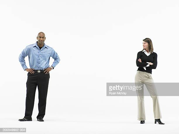Man and woman standing apart, woman looking at man