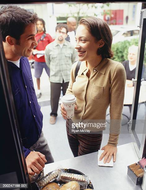 Man and woman standing at outdoor coffee cart