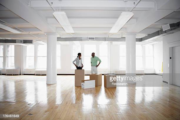 Man and woman standing by boxes in empty office