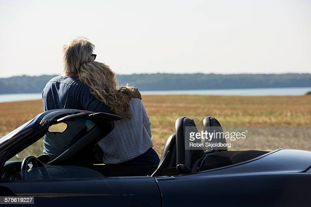 Man and Woman standing by car looking at view