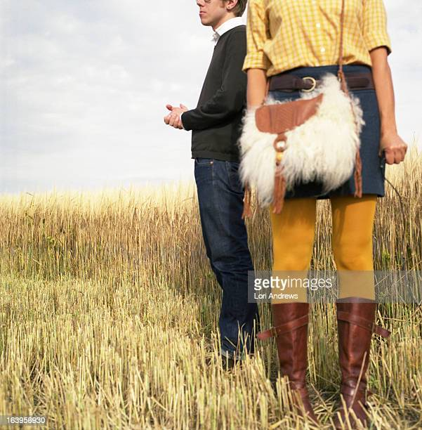 Man and woman standing in a golden wheat field