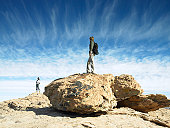 Man and woman standing on boulders