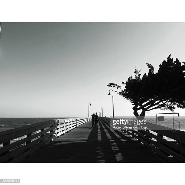 Man And Woman Standing On Pier Over Sea Against Clear Sky