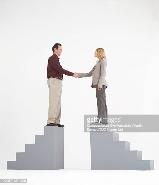 Man and woman standing on top of stairs, shaking hands, side view