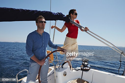 Man and woman steering yacht, Dalmatia, Adriatic sea : Stock Photo