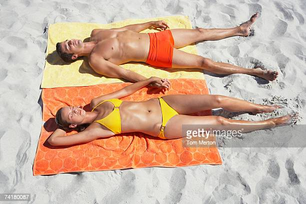 Man and woman sunbathing on beach towels in sand