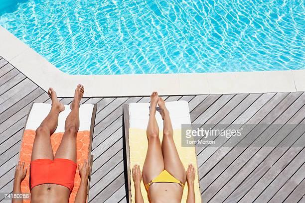 Man and woman sunbathing on pool deck waist down