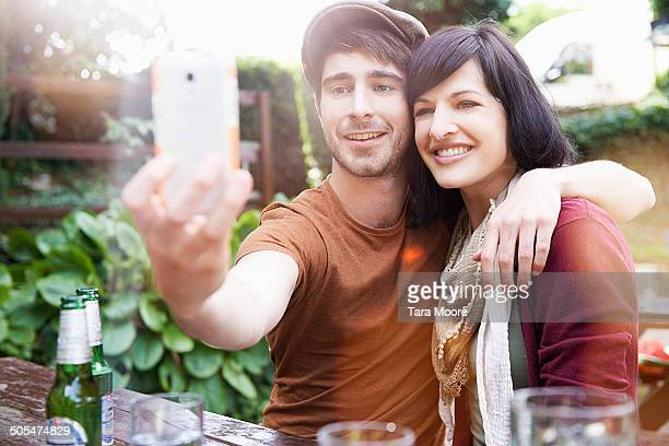 man and woman taking selfie in beer garden