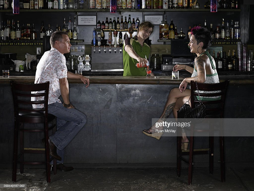 Man and woman talking at bar, bartender pouring cocktail in background : Stock Photo