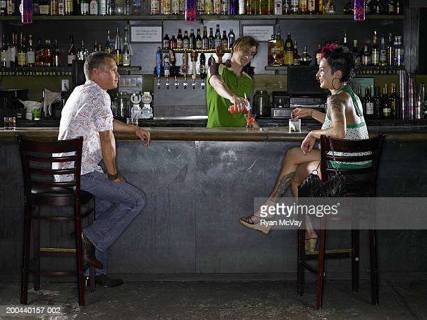 Man and woman talking at bar, bartender pouring cocktail in background