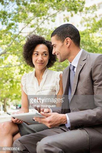 Man and woman talking in park : Stock Photo