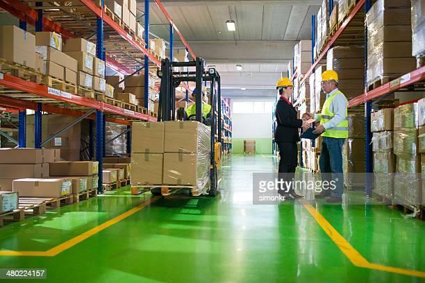 Homme et femme parlant dans un entrepôt rempli de colis