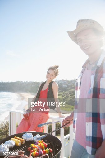 Man and woman tending barbecue with ocean in background : Stock Photo