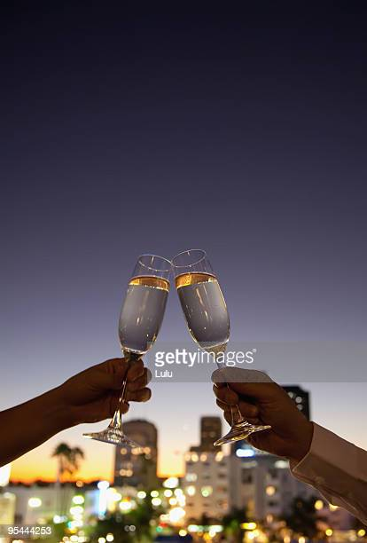 Man and woman toasting with champagne on rooftop