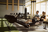 Fit couple having training on rowing machines in gym together.