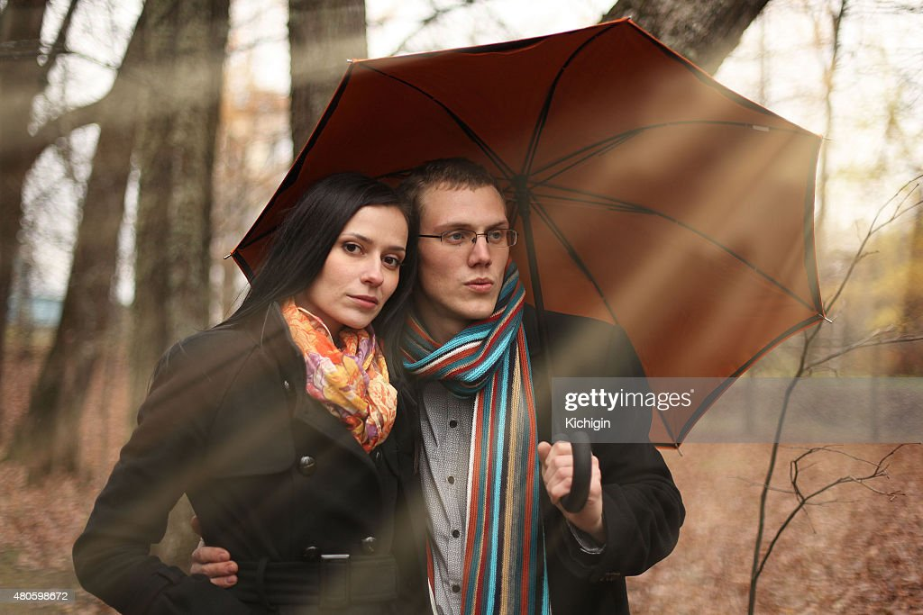 man and woman under an umbrella in the autumn forest : Stock Photo