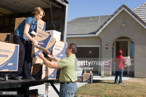 Man and woman unloading truck of cardboard boxes : Stock-Foto